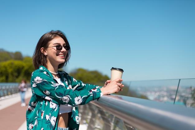 Outdoor portret van vrouw in groen shirt met kopje koffie genieten van zon, staat op de brug met geweldig uitzicht op de stad in de ochtend