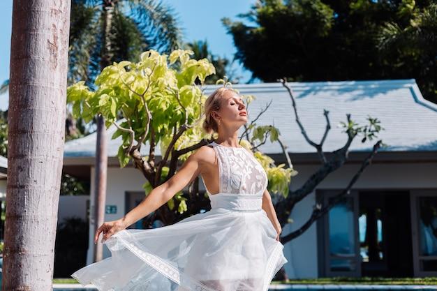 Outdoor portret van vrouw in witte trouwjurk in villa in zonnige dag, tropische weergave