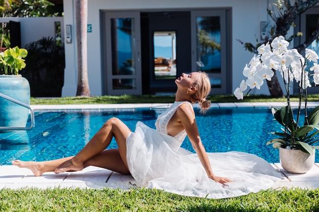 Outdoor portret van vrouw in witte trouwjurk zitten in de buurt van blauwe zwembad met bloemen orchidee