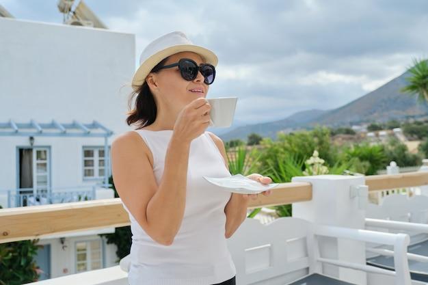 Outdoor portret volwassen mooie vrouw met kopje drankje, gelukkig mooie rijpe vrouw rusten in restaurant op zonnige zomerdag