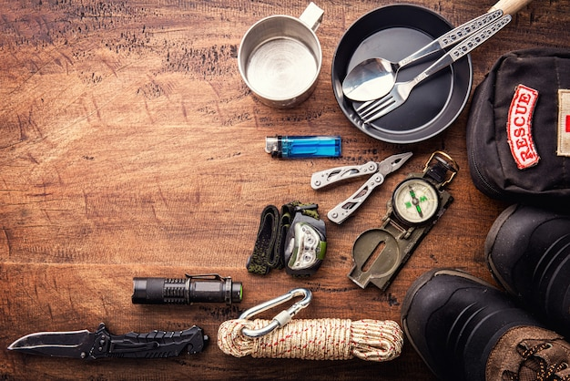 Outdoor reisuitrusting planning voor een berg trekking camping reis op houten achtergrond. bovenaanzicht - vintage film korrel filter effect stijlen