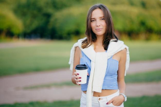 Outdoor shot van brunette vrouw, gekleed in casual t-shirt, witte broek, houdt hand in zak, drinkt aromatische koffie tijdens ochtendwandeling