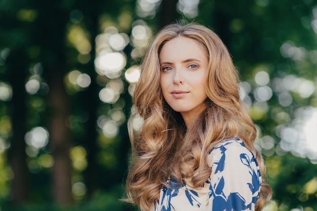 Outdoor shot van mooie europese vrouw heeft licht krullend haar, pure huid en blauwe ogen, gekleed in modieuze zomerjurk