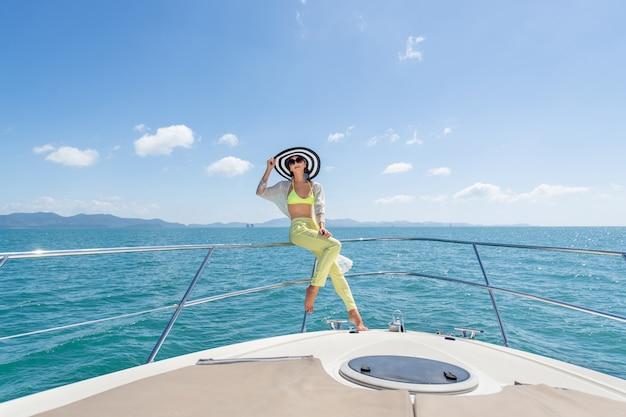 Outdoor shot van schattige jonge vrouw in een zomer pak en hoed zittend op de rand van jacht