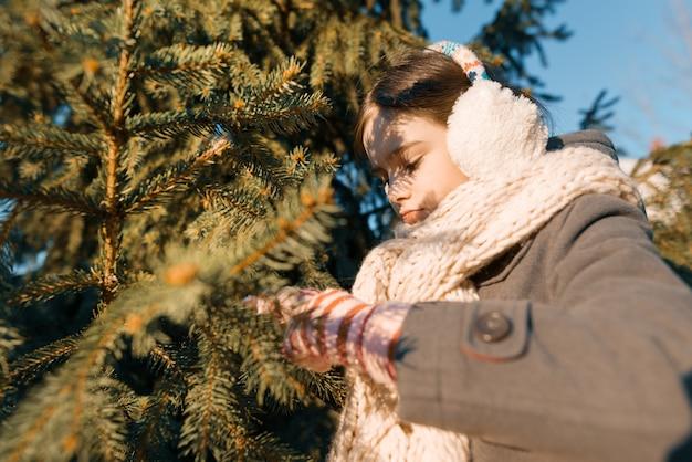 Outdoor winter portret van een klein lachend meisje in een gebreide sjaal