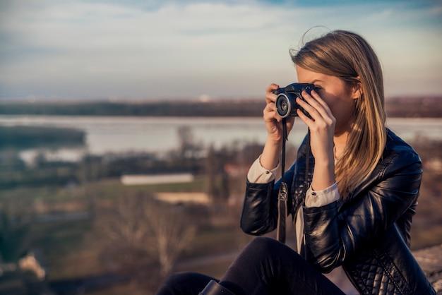 Outdoor zomer lachende levensstijl portret van mooie jonge vrouw plezier in de stad in europa in de avond met camera reis foto van fotograaf foto's maken