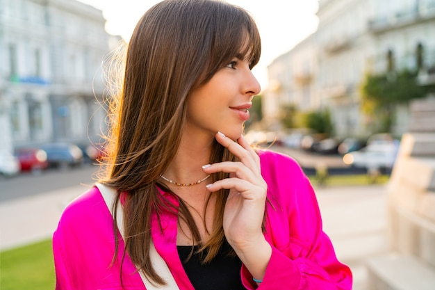 Outdoor zomer portret van debonair knappe vrouw in stijlvolle roze jas.