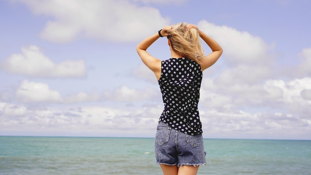 Outdoor zomer portret van jonge mooie vrouw op zoek naar de oceaan op tropisch strand, geniet van haar vrijheid en frisse lucht