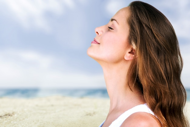 Outdoor zomer portret van mooie jonge lachende gelukkige vrouw poseren in de buurt van de zee