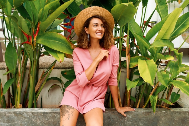 Outdoor zomer portret van verleidelijke brunette vrouw met golvende haren in roze jurk poseren