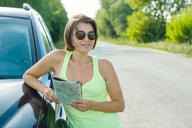 Outdoor zomer portret van volwassen vrouw met kaart