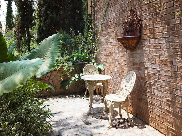 Outdoor zomertuindecoratie met vintage stoelen en tafelmeubilair.