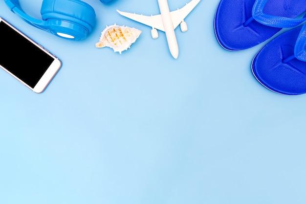 Outfit en accessoires van reiziger op blauwe achtergrond met kopie ruimte.