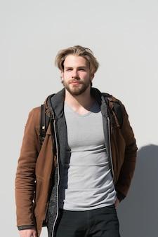 Outfit, mode, casual stijl. man draagt bruine jas, t-shirt, broek op grijze muur. macho met baard op ongeschoren gezicht en blond haar.