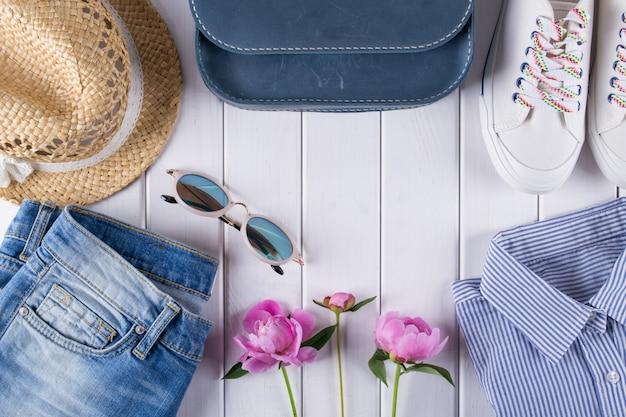 Outfit van casual vrouw. collage op wit met shirt, spijkerbroek, bril, sneakers, handtas, hoed, pot