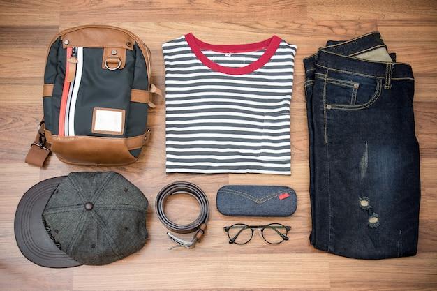 Outfits van reiziger, jongen, man, casual outfits voor heren op houten plank achtergrond