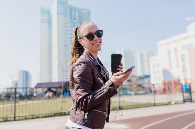 Outsdie portret van charmante lachende mooie vrouw met donker haar gekleed lederen jas en zwarte zonnebril luisteren naar muziek in oortelefoons
