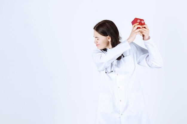 Ov-zijaanzicht van jonge vrouwelijke arts die haar kleine geschenkdoos met haar beide handen vasthoudt