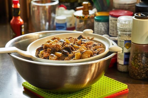 Ovengebakken aubergines bezinken in zeef op een kom.