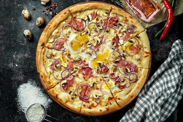 Ovengebakken italiaanse pizza met witte saus, kaas, ham, champignons en rauwe dooiers in een compositie met ingrediënten op een donkere tafel. uitzicht van boven. pizza carbonara