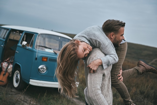 Over de oren verliefd. knappe jonge man die zijn aantrekkelijke vriendin op de schouders draagt en glimlacht terwijl hij in de buurt van de blauwe minibus in retrostijl staat