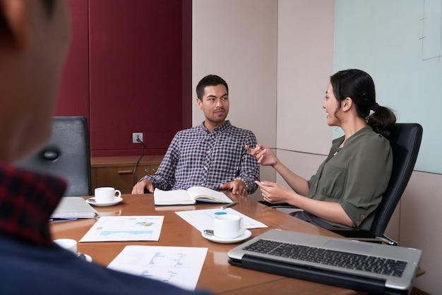 Over de schouder bekeken van business team brainstormen tijdens de korte vergadering