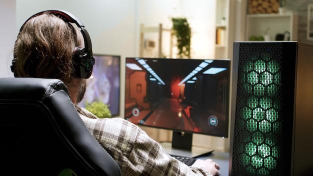 Over de schouder geschoten van een man met lang haar die schietspellen speelt terwijl hij op een speelstoel zit.
