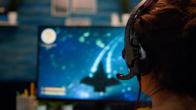 Over de schouder pro gamer vrouw spelen computer fps shooter video game op kampioenschap, praten in headset. cyber presteert op krachtige computer in stijlvolle kamer tijdens gametoernooi