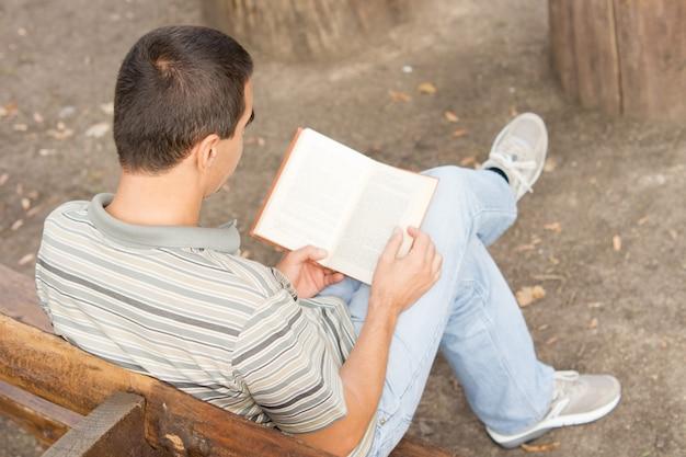 Over de schouder van een man in vrijetijdskleding, zittend op een bank die een boek leest en neerkijkt op de open pagina's