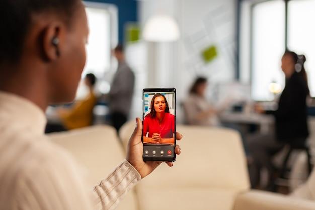 Over de schouder van zwarte werknemer die met partner praat tijdens een videogesprek met behulp van de telefoon in een startkantoor