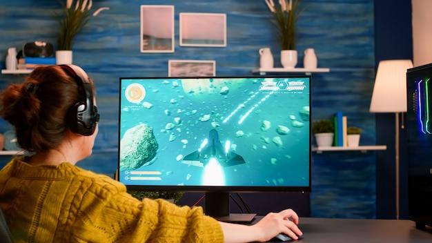 Over de schouder vrouwelijke gamer die 's avonds laat online professioneel schietspel op de computer speelt computer