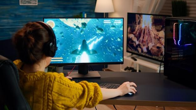 Over de schouder vrouwelijke gamer die 's avonds laat online professioneel schietspel op de computer thuis speelt. professionele speler die online videogames test op pc met modern technologienetwerk draadloos.