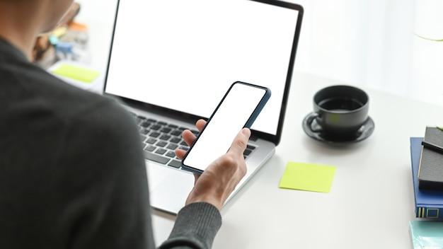 Over de schouder weergave van jonge man freelancer met behulp van mobiele telefoon en werken met computer laptop op moderne werkplek.