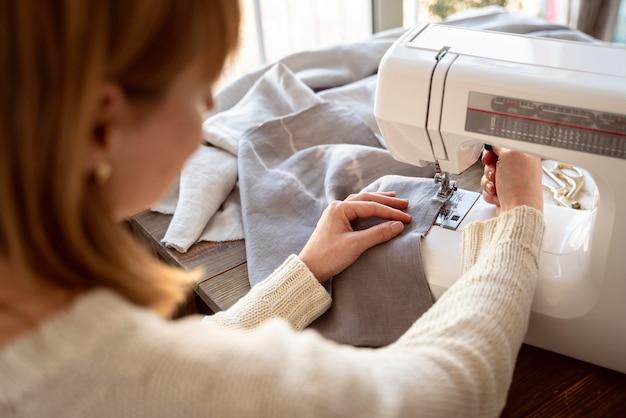 Over de schouder weergave van kleermaker vrouw met behulp van naaimachine