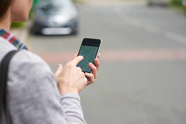 Over de schouderweergave van een onherkenbare persoon die taxi volgt op de mobiele app