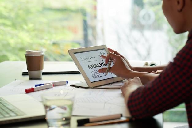 Over de shoukder-weergave van een onherkenbare persoon die analysetabel op tablet-pc onderzoekt