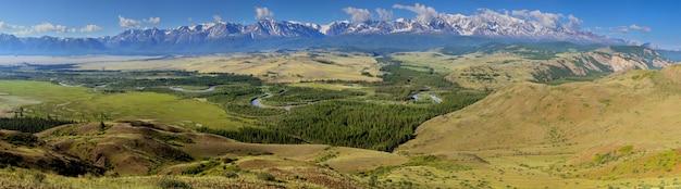 Over het bergdal, met sneeuw bedekte toppen in de wolken en groene zomerhellingen