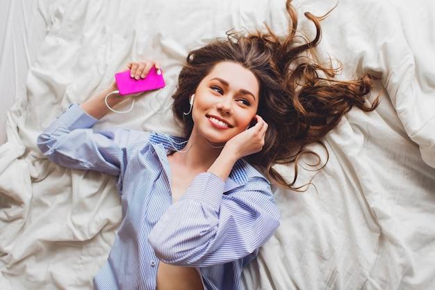 Over het hoofd portretmening van een jonge vrouw die op haar bed bepaalt
