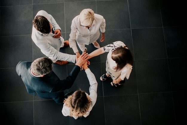 Over mening bij groep bedrijfsmensen die handen samen houden