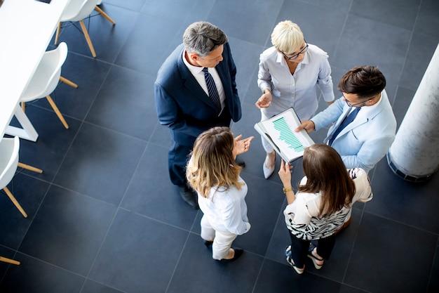 Over mening bij groep zakenlui die zich in het bureau bevinden en plan analyseren