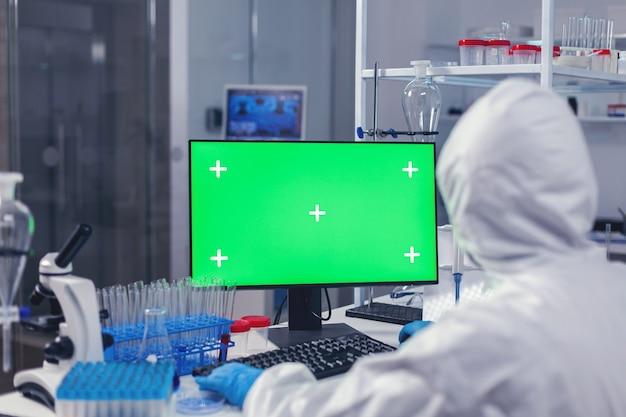 Over schouder schot van arts die werkt aan coroanvirusvaccin met behulp van computer met groen scherm gekleed in ppe. team van microbiologen die vaccinonderzoek doen en schrijven op een apparaat met chroma key, geïsoleerd,