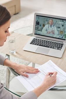 Over schouder weergave van ernstige jonge vrouw papieren invullen en laptop gebruikt tijdens een gesprek met arts via videoverbinding