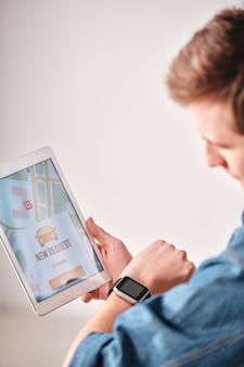 Over schouder weergave van jonge man tijd op slimme horloge controleren tijdens het bestellen van taxi online via tablet-app