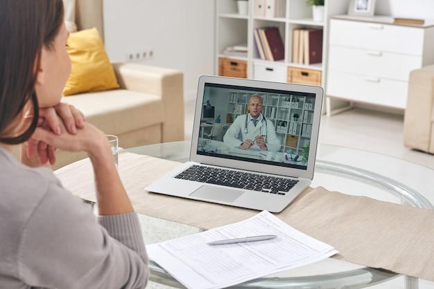 Over schouder weergave van jonge vrouw zittend aan tafel in de woonkamer en met behulp van laptop voor online overleg met arts