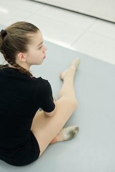 Over schouder weergave van nieuwsgierige eenzame tienermeisje zittend op de vloer en kijken naar repetitie in de sportschool