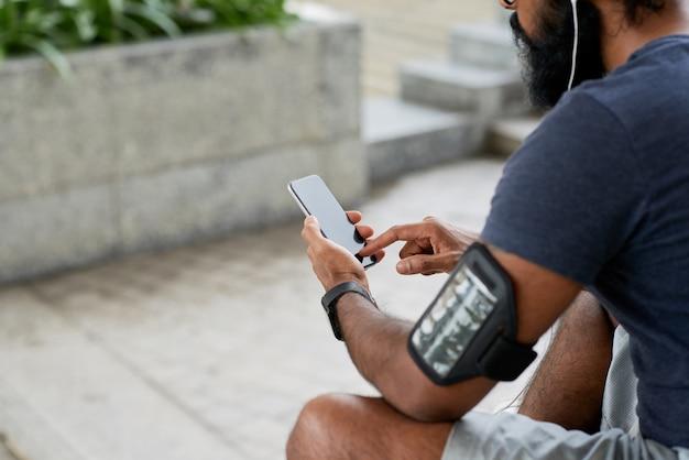 Over schouder zicht op jonge indiase man met baard die buiten zit en fitness-app op smartphone gebruikt