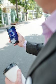 Over schouder zicht op onherkenbare man in jas die koffie drinkt en de weersvoorspelling op de telefoon controleert terwijl hij over straat loopt