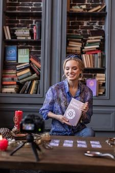 Over vedische vrouw. vrolijke jonge vrouw die lacht terwijl ze een interessant boek voor de camera houdt