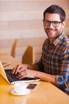 Overal de mogelijkheid hebben om te werken. knappe jonge man die op laptop werkt en glimlacht terwijl hij in café zit