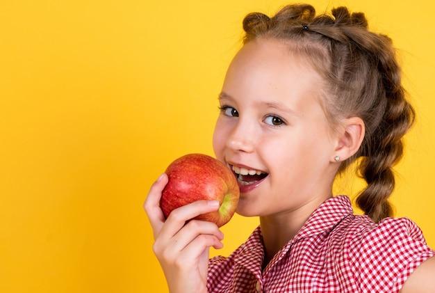 Overal lente. lente seizoen fruit. vol vitamines. alleen biologisch voedsel. natuurlijk en gezond. gelukkige jeugd. kind eet appel. kind met fruit. tienermeisje dat appels bijt. herfst oogst.